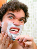 man shaving and grimacing